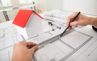 Close-up Of Engineer Drawing Diagrams In Front Of House Model On Blueprint