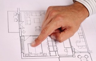 Architect showing project, house plans. Close up on male hand pointing at plan